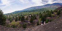 Panoramic photo of tourists hiking on an old lava flow, Mount Etna Volcano, Sicily, UNESCO World Heritage Site, Italy, Europe. This is a panoramic photo of tourists hiking on an old lava flow at Mount Etna Volcano, Sicily, UNESCO World Heritage Site, Italy, Europe.