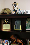 A shelf with a figurine showing an officer protecting a child along with other awards in the office of Chief Deputy Donald Lowe of the Louisa County Sheriff's Office.