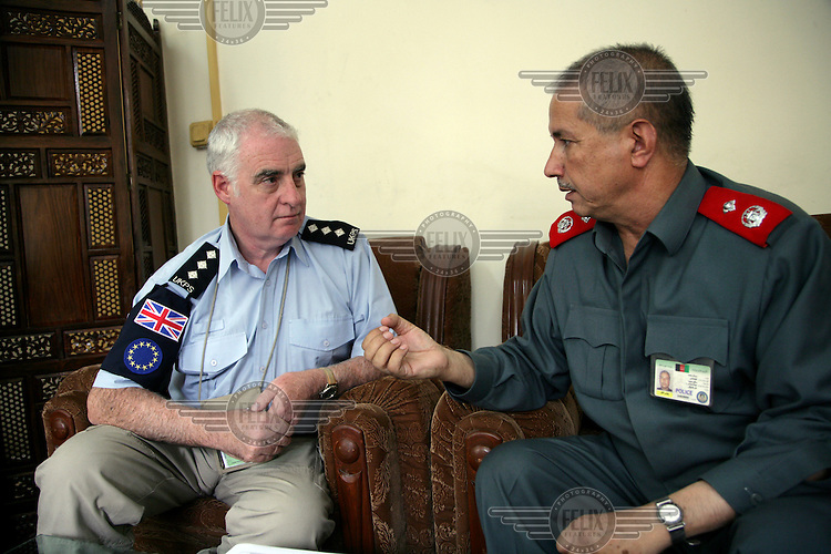 British police officer Andy Carter mentors Afghan Police General Kohmandi in his office at the Ministry of Interior...