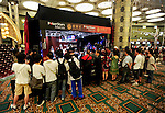 The crowd gathered around the final table TV set.