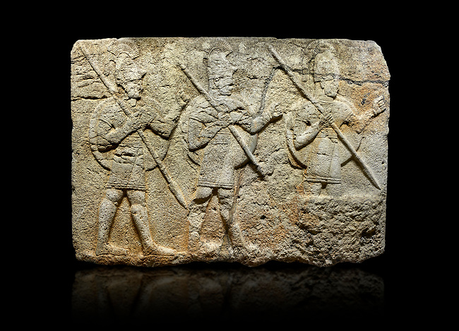 Hittite monumental relief sculpted orthostat stone panel from the Herald's Wall. Basalt, Karkamıs, (Kargamıs), Carchemish (Karkemish), 900-700 B.C. Military parade. Anatolian Civilisations Museum, Ankara, Turkey. Two helmeted soldiers in short skirts carry the shield on their backs and the spears in their hands.  <br /> <br /> Against a black background.