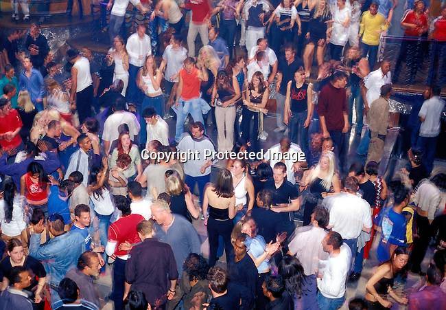 dippnig00060 People Nightlife. People dancing the night away on a crowded dance floor on August 25, 2002 at the Dockside nightclub, one of the biggest and most popular in Cape Town, South Africa. Thousands of people come every weekend to enjoy themselves..©Per-Anders Pettersson/ iAfrika Photos.