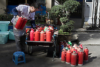 A worker delivers hot water in kettles to a local restaurant in Nanjing, Jiangsu province, China, November 2012.
