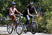 United States President Barack Obama (R) and daughter Malia Obama, 13, bike together on a bike path through Manuel F. Correllus State Forest in West Tisbury, Massachusetts while vacationing on Martha's Vineyard on August 23, 2011.   .Credit: Matthew Healey / Pool via CNP