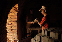 Two men move bricks out from the furnace in a brickkiln in Bazhou, Hebei provinc, China..04-SEP-04