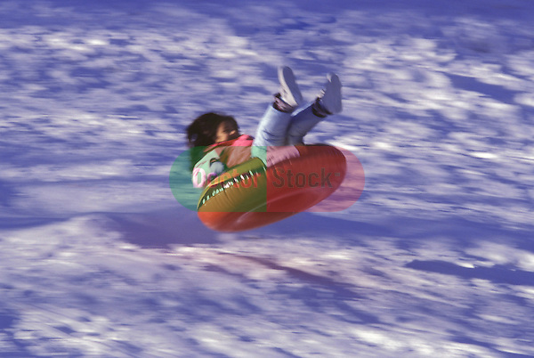 Child slides in snow on rubber inner tube toy.