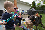 Sarah blows bubbles with Nathan and Katelyn in the back yard while their dog, Max, waits to catch the bubbles in his mouth. Sarah takes the triplets outside to play almost every day.
