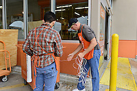 MIRAMAR, FL - OCTOBER 06: Two Home depot employee getting rope to helping customer tie they plywood to they car as South Florida residents prepare for Hurricane Matthew by purchasing plywood at Home Depot on October 6, 2016 in Miramar, Florida. The hurricane is expected to make landfall sometime this evening or early in the morning as a possible category 4 storm.Credit: MPI10 / MediaPunch