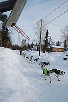 Allen Moore passes a basketball hoop on the road as he arrives into the Shageluk checkpoint on Saturday morning    Iditarod 2009