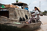 A woman sits in a small boat alongside a larger one on the Hau River in the Mekong Delta, south of Can Tho, Vietnam. Sept. 30, 2011.