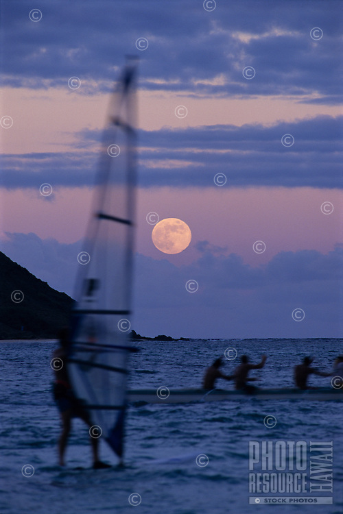 Sailboard and Hawaiian outrigger canoe at moonrise near Lanikai beach, Oahu, Hawaii.