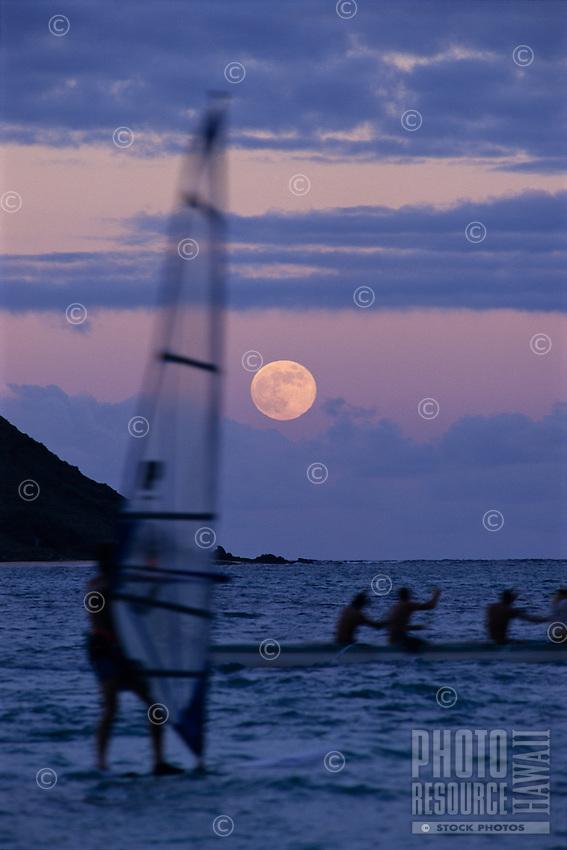 Sailboard and Hawaiian outrigger canoe at moonrise near Lanikai beach, Oahu, Hawaii.