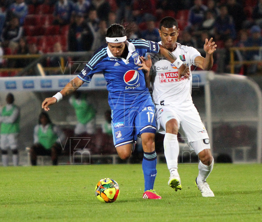 BOGOTA -COLOMBIA. 19-02-2014. Dayro Moreno (Izq) de Millonarios  disputa el balon contra Juan Cabezas del Once Caldas  durante el partido por la sexta fecha de La liga Postobon 1 disputado en el estadio El Campin. /Dayro Moreno (L) fights for the Millionarios Juan Cabezas balloon against Once Caldas during the game for the sixth round of the Postobon one league match at El Campin Stadium. Photo: VizzorImage/ Felipe Caicedo / Staff