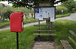 Small rural settlement services comprising of community noticeboard, wooden benches, post box, Playford, Suffolk, England