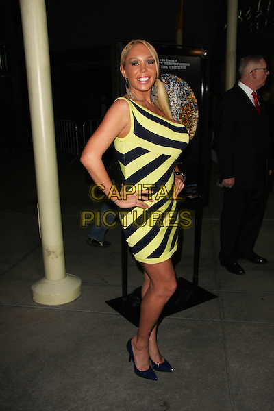"MARY CAREY.""I Am"" Los Angeles Premiere Held at The Arclight Theater, Hollywood, California, USA..March 8th, 2011.full length dress black yellow one shoulder ponytail dress hands on hips side.CAP/ADM/TB.©Tommaso Boddi/AdMedia/Capital Pictures."