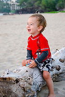 A one-year-old part-Asian boy plays on a log at a beach on the Island of Hawai'i.