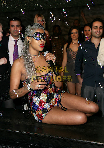 """KELIS.Kelis Performs Her New single """"Acapella"""" at Eve Nightclub in Crystals at CityCenter, Las Vegas, Nevada, USA,.26th February 2010..music gig singing microphone concert performing half length mask strapless sequined gold red blue multi-coloured playsuit sequin diamond pattern patterned hand sitting down bubbles  beads bracelet necklace chain.CAP/ADM/MJ.©Michael Jade/Admedia/Capital Pictures"""