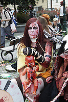 Woman participating in the Zombie walk in Prague 2014, sitting on a bench with a doll on her lap. The Doll still has the umbilical cord attached, and has make up blood on.