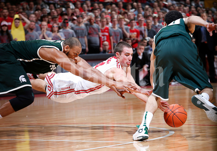 Michigan State Spartans guard Travis Trice (20) grabs the ball as Ohio State Buckeyes guard Aaron Craft (4) tries to dive for it in the second half of the NCAA men's basketball game between the Ohio State Buckeyes and the Michigan State Spartans at Value City Arena in Columbus, Ohio, Sunday afternoon, March 9, 2014. The Ohio State Buckeyes defeated the Michigan State Spartans 69 - 67. (The Columbus Dispatch / Eamon Queeney)