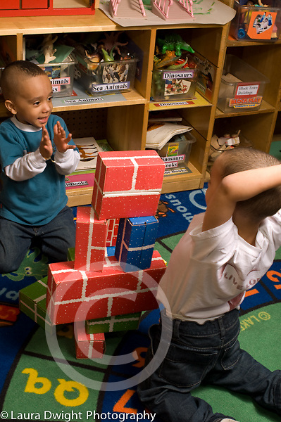 Day Care Center 2-3 year olds two boys working together building with cardboard blocks, boy clapping when finished