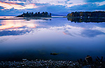 Idaho, North, Idaho Panhandle, Sandpoint. Calm water on Lake Pend Oreille and Fishermans Island in Oden Bay under an autumn sunset.
