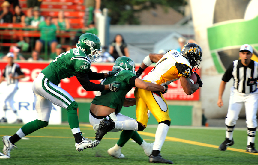 Hamilton Tiger-Cats wide receiver Arland Bruce III fights off two defenders for a fourth quarter touchdown against the Saskatchewan Roughriders during CFL action in Regina Saturday, July 31, 2010. THE CANADIAN PRESS/Mark Taylor.