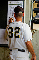 Wake Forest Demon Deacons head coach Tom Walter #32 marks changes on the lineup card during the completion of the suspended game from March 23rd against the Florida State Seminoles at Wake Forest Baseball Park on March 24, 2012 in Winston-Salem, North Carolina.  The Seminoles defeated the Demon Deacons 5-4 in 11 innings.  (Brian Westerholt/Four Seam Images)