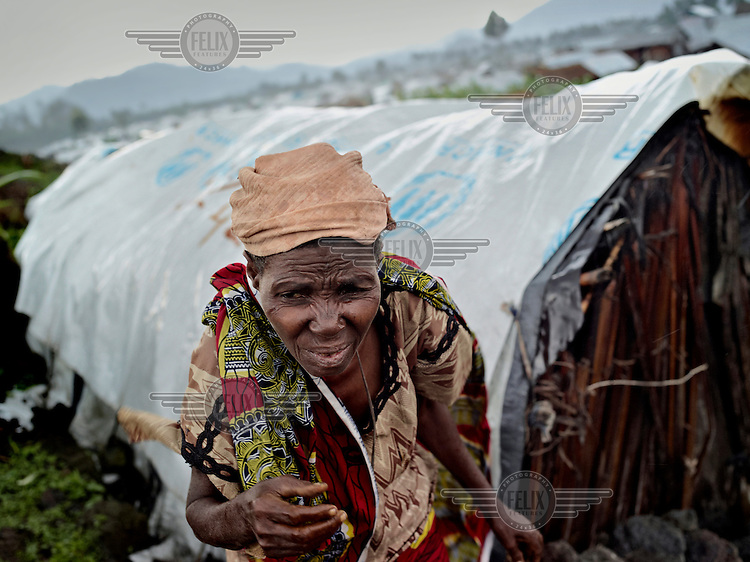 67 year old Saniya Kasigwa takes cover from the rain while she tries to fix the plastic sheets that function as the roof on her hut at a UN IDP camp near Goma.