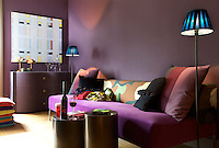 The walls of the living room have been painted in deep shades of fig and prune and the sofa is covered in velvet to match