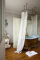 """In the luxurious bathroom the bath is draped """"a la Polonaise"""" and behind it the wall is painted in a trompe l'oeil design"""