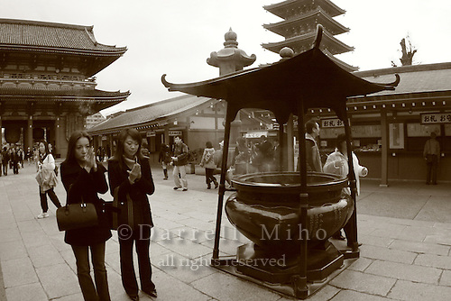 Mar 6, 2006; Tokyo, JPN; Asakusa.Visitors gather around a large bronze incense bowl in front of the Senso-ji Buddhist temple (not pictured) and waft the smoke (considered to be the breath of the gods) upon themselves for its supposed curative powers...The Gojuno-to (five storied pagoda) can be seen in the background...Photo credit:  Darrell Miho