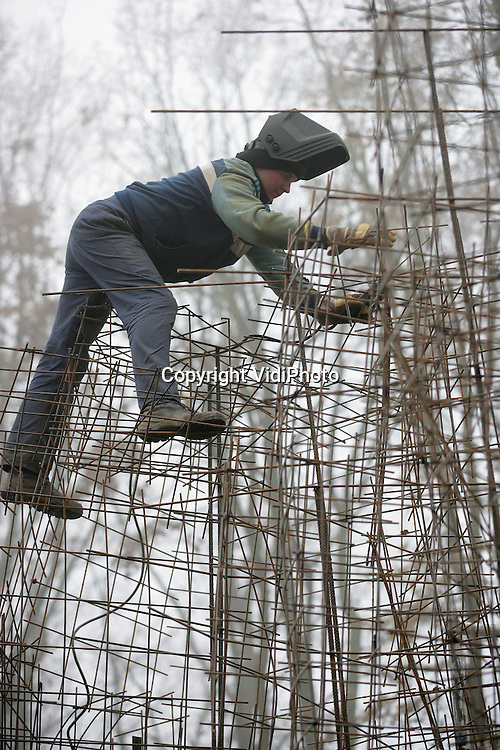"""Foto: VidiPhoto..RHENEN - Een lasser balanceert boven op een woud van lichte wapening. De metalen pinnen worden aan elkaar gelast als basis voor een betonnen rotsmuur, onderdeel van het nieuwe leeuwenverblijf in Ouwehands Dierenpark in Rhenen. Het park is op dit moment bezig met een enorme uitbreiding: """"Een ontmoeting met Afrika."""" Voorjaar 2005 moet de nieuwe attractie gereed zijn. Hoofdaannemer van het project is Koenen uit Nijmegen."""