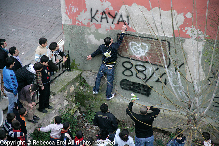Grafitti being sprayed in a Beyoglu back street in Istanbul, Turkey. A boy's name and his date of birth are sprayed on a wall as a memento before he goes off for his military service.