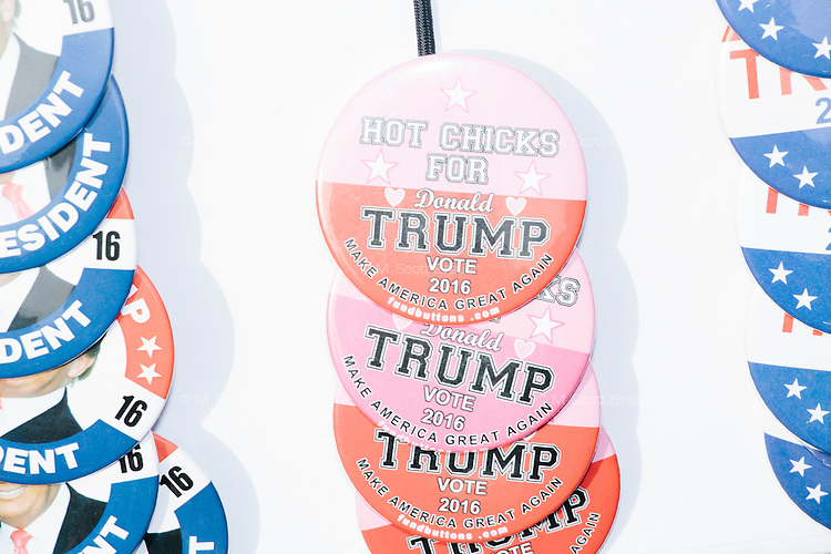 "An independent merchandise seller displayed pro-Trump campaign buttons, shirts, and hats, outside the venue after real estate mogul and Republican presidential candidate Donald Trump spoke at a rally at Exeter Town Hall in Exeter, New Hampshire, on Thurs., Feb. 4, 2016. Buttons had slogans such as ""Trump for President,"" ""Hot Chicks for Trump,"" and ""Hillary for Prison."""