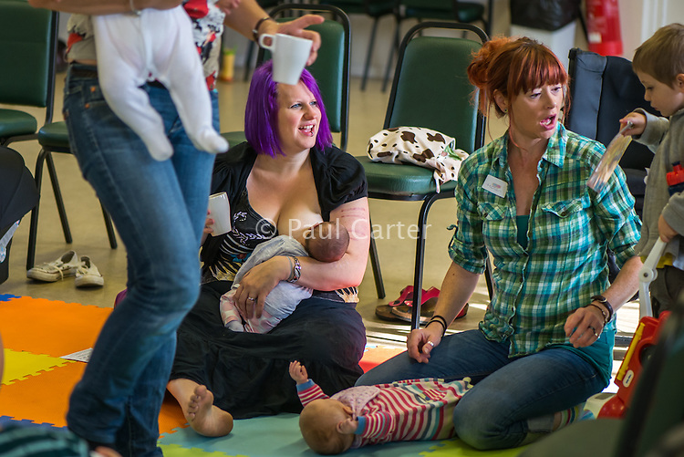 Breastfeeding a newly arrived baby at a singing and signing group whilst talking to the other mothers.Image from the breastfeeding collection of the &quot;We Do It In Public&quot; documentary photography picture library project: <br />  www.breastfeedinginpublic.co.uk<br /> <br /> <br /> Berkshire, England, UK<br /> 27/09/2013<br /> <br /> &copy; Paul Carter / wdiip.co.uk