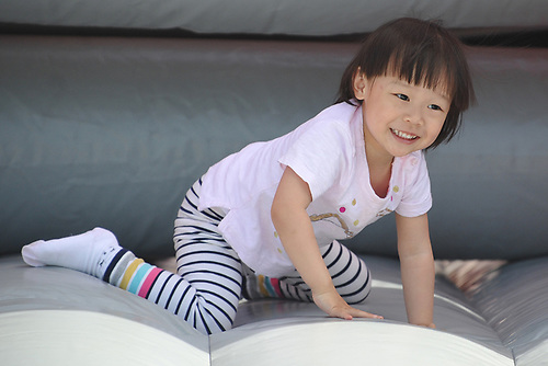 Sophie Gong, 3, of Garden City has fun on an inflatable obstacle course during Long Island Marathon Weekend festivities at Eisenhower Park on Saturday, May 5, 2018.