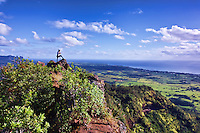 Just after sunrise, a hiker takes in the view from the chin of the Sleeping Giant mountain ridge near Wailua, Kaua'I.