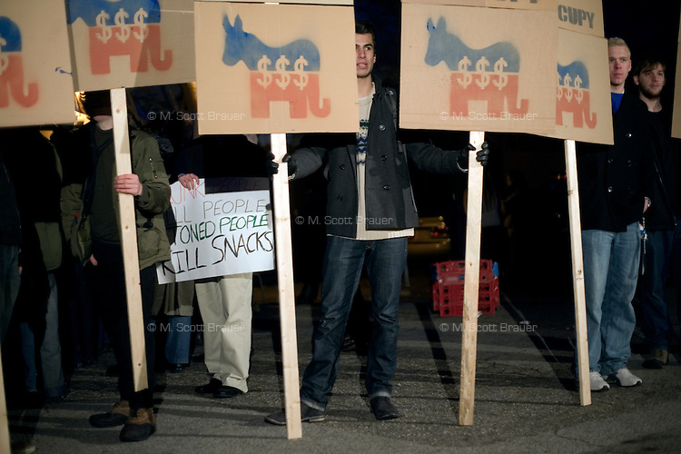 Occupy New Hampshire protesters stand at the edge of the crowd as former senator Rick Santorum speaks to a crowd made primarily of media and protestors outside Belmont Hall and Restaurant in Manchest, New Hampshire, on Jan. 6, 2012.  Santorum is seeking the 2012 GOP Republican presidential nomination.  Protestors were primarily from the Occupy New Hampshire group..