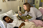Chaplain Ann Moore reads verses from the Bible patients Henry Eric in the AIDS ward of the San Francisco General Hospital, California