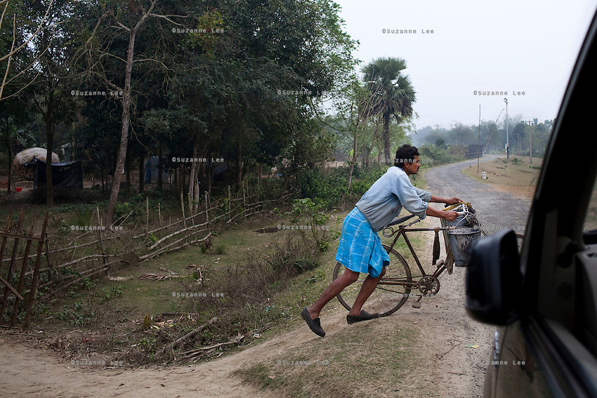(NO BYLINE: PHOTOGRAPHED IN RESTRICTED AREAS WITHOUT GOVT. PERMISSION) A villager pushes his bicycle as he leaves his home in the 'no mans land' zone on the left of the fence of the India-Bangladesh Border fence, in Nadia district, Ranaghat, North 24 Parganas, West Bengal, India, on 19th January, 2012. On the left of the fence, villagers live in the 'no mans zone'. People and products like cows are often smuggled across the porous borders by wading across the rivers and jumping the fences. Recently, a woman was shot dead by the Indian Border Security Force as she was climbing over a fence, and was left on the fence for 3 days.