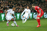SWANSEA, WALES - MARCH 16: Wayne Routledge of Swansea (L) attempts to get a cross past Alberto Moreno (R) of Liverpool during the Premier League match between Swansea City and Liverpool at the Liberty Stadium on March 16, 2015 in Swansea, Wales