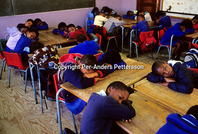 education,school,kids,.Children take a nap while waiting for their teacher to arrive to an overcrowded classroom on June 17, 2004 in Yomelela primary school in Khayelitsha, the biggest black township, about 20 miles outside Cape Town, South Africa. Some of the children dance in a ballet school called Dance For All, which teaches about 200 unprivileged children dance after school. Many children are talented and the discipline taught during the dance classes has helped many to improve their concentration in school. .©Per-Anders Pettersson/iAfrika Photos.......