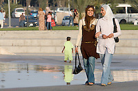 Tripoli, Libya, North Africa - Modern Dress Styles in Contemporary Libya.  Walking in a Public Park near the Green Square, in downtown Tripoli.  Women typically cover their heads with a scarf, but may wear jeans, levis, or a traditional abaya, a loose-fitting, ankle-length outer garment.  Touching or hand-holding in public, both between the sexes and among women is common.