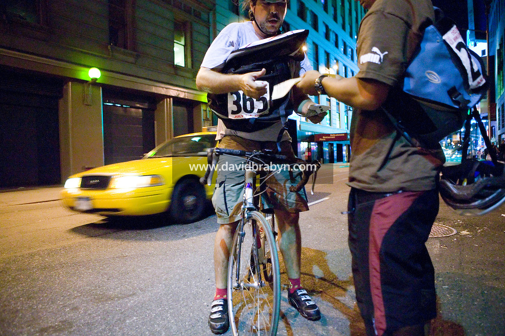 3 July 2005 - New York City, NY, USA - A rider gets his manifest stamped by &quot;Junjun&quot; (R) at an alleycat checkpoint on 43rd street in New York City, USA, July 3rd 2005. Alleycats are urban cycle races held informally - without notification of the authorities - on open roads and in real traffic, to simulate the messenger's working conditions. Photo Credit: David Brabyn<br />
