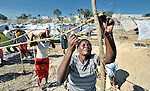 A woman fastens sticks together with recycled wire as she builds a temporary home in a spontaneous camp for quake survivors being established in Croix-des-Bouquets, Haiti, north of the capital Port-au-Prince. Quake survivors continue to move as aftershocks continue, and reports of aid deliveries in one camp will provoke families from other camps to migrate there.