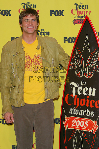 JIM CARREY.Teen Choice Awards,.The Gibson Amphitheatre,.Universal City, 14th August 2005.half length brown trousers yellow t-shirt green jacket black red surf board smile smiling.www.capitalpictures.com.sales@capitalpictures.com.© Capital Pictures.