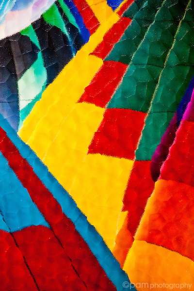 colorful abstract of hot air balloons taken under textured glass