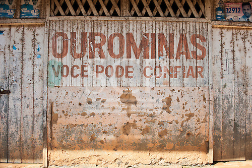 """Xingu River, Para State, Brazil. The Volta Grande; Ressaca settlement, old garimeiro illegal gold-mining town. Bullet holes on the wall; the sign says """"Ourominas, you can trust""""."""