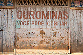 "Xingu River, Para State, Brazil. The Volta Grande; Ressaca settlement, old garimeiro illegal gold-mining town. Bullet holes on the wall; the sign says ""Ourominas, you can trust""."