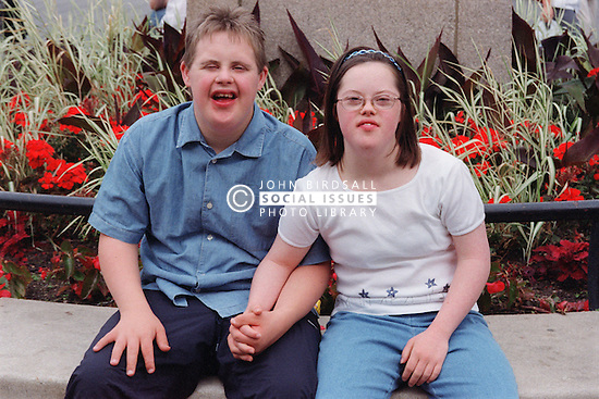 Teenage boy and girl with Downs Syndrome sitting together in park holding hands,